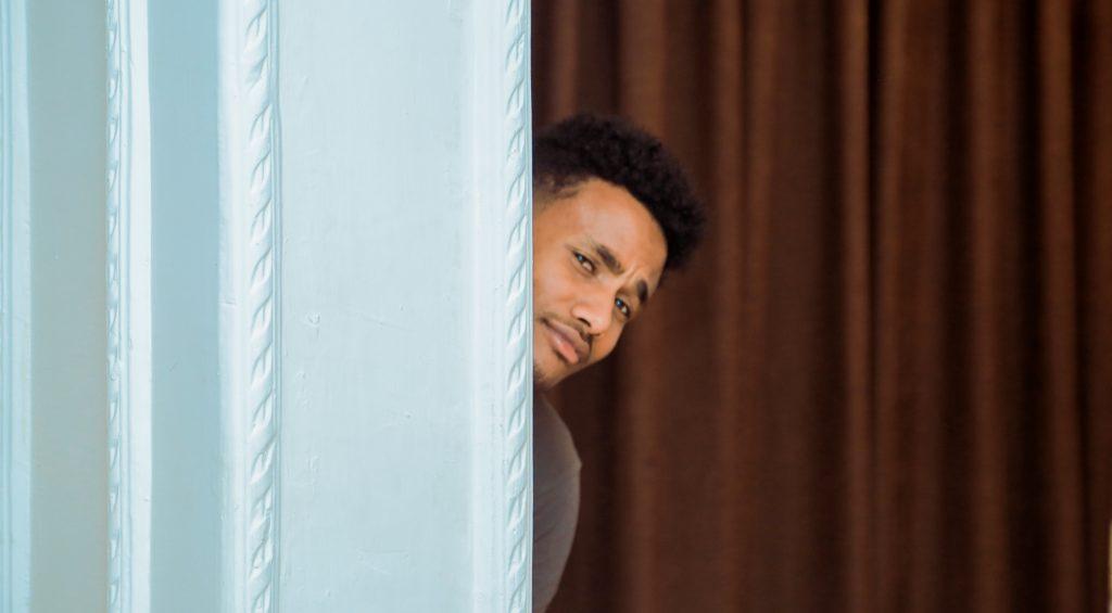Man peeking from behind curtain